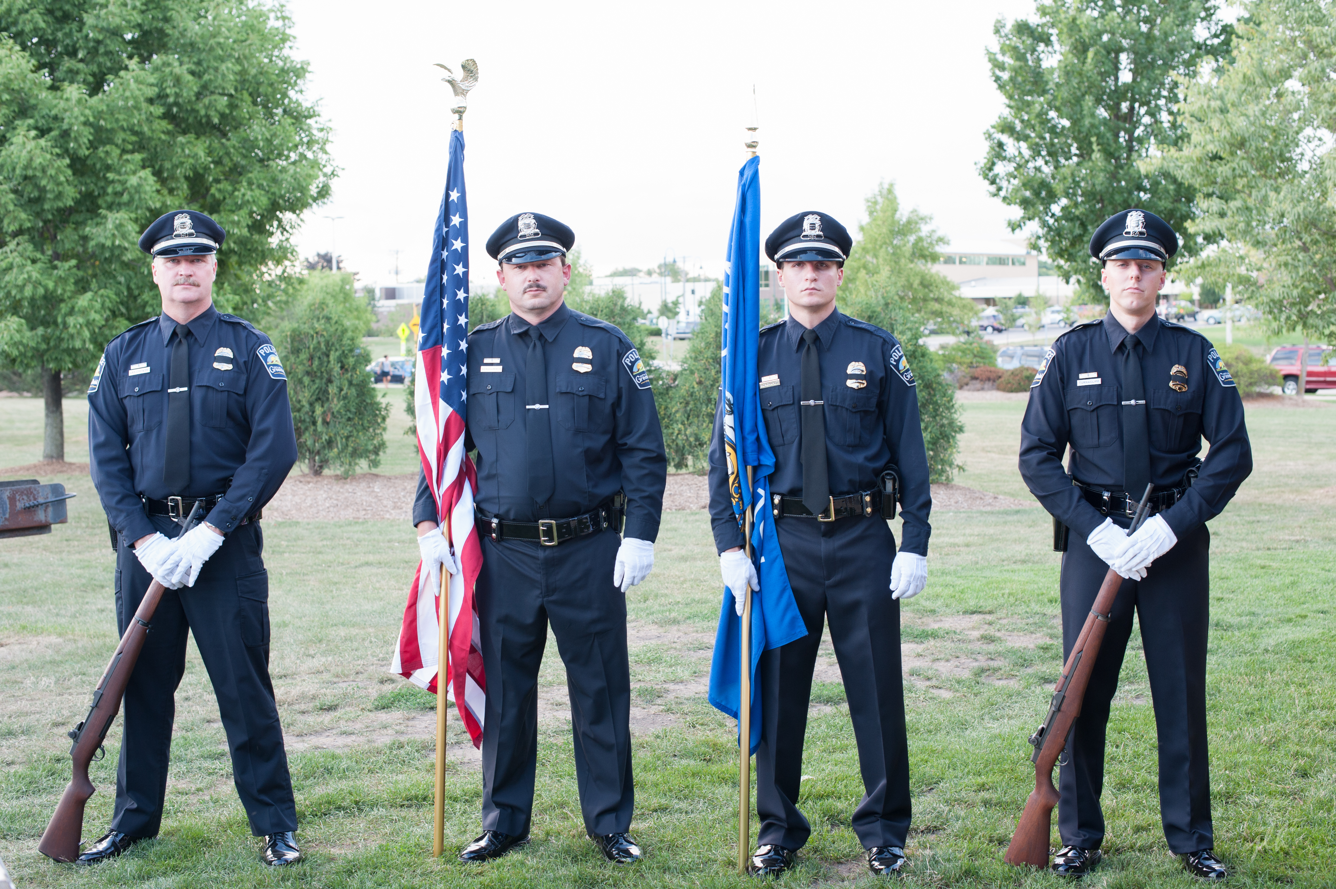 4 police officers presenting the American flag and another flag at a ceremony