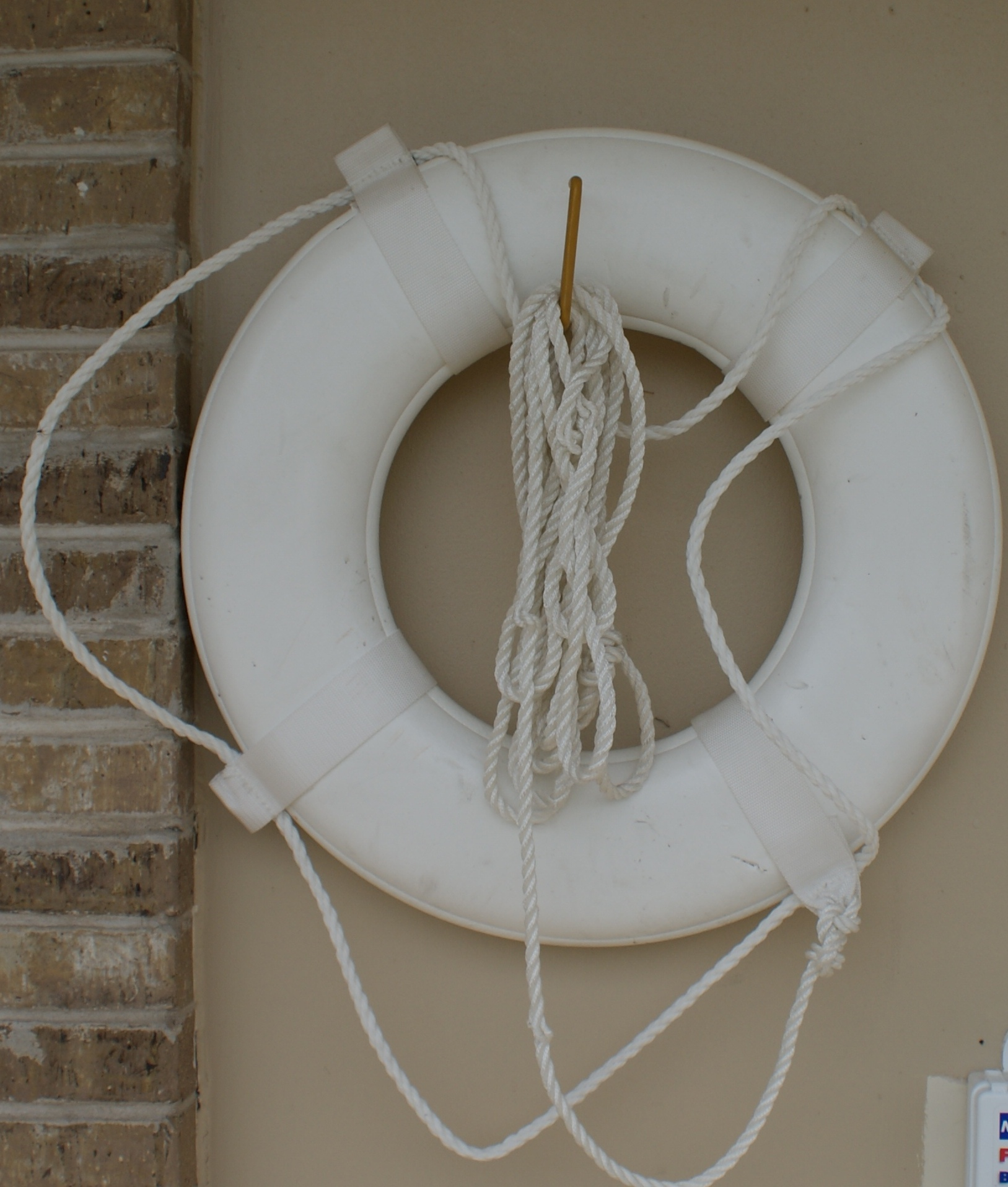 A white pool life saver hangs on a wall with ropes around it.