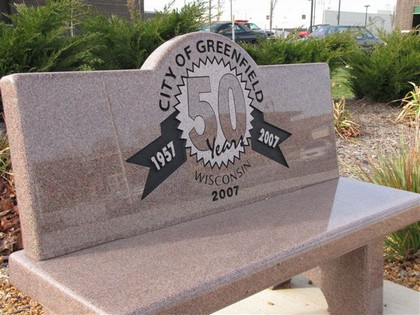 A granite bench with the City of Greenfield 50th Anniversary logo etched on the back.