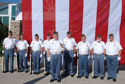 A group of men stands in front of a large American flag to honor those that gave their lives on 9/11.