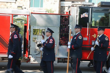 Members of the Fire Department march in a line in front of the fire truck.