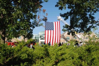 A photograph of the large American flag, held between 2 ladder trucks, as seen behind a few bushes and trees.