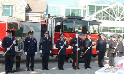 A line of fire fighters stand at attention in front of a fire truck, some with axes.