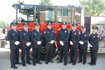 2 members of the police department stand with 6 members of the fire department for a portrait in front of a fire truck.
