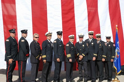 10 members of the Greenfield Fire Department stand in a line for a portait in front of the American Flag.