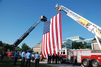 Police officers and fire fighters gather as 2 ladder trucks raise a large American flag between them.